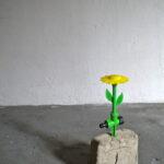 Liliana Moro, Fiore (fontanina) 2013. Argilla, fiore in platica a getto d'acqua, tubo di gomma verde, acqua. Courtesy Liliana Moro