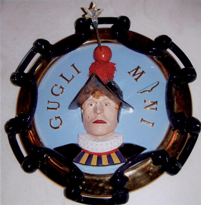 Luigi Ontani, Guglielmo Marconi Tell, tondo in ceramica, 1996. Ontani si autoritrae nei panni dell'eroe svizzero, con l'elmo in testa. E' proprio l'elmo a costituirsi però anche come elemento del rebus, collocandosi dopo le lettere G, U, G, L ed I (da cui GUGLI-elmo). A seguire, la parola Marconi è formata dalla M, dall'immagine di un arco (l'arco di Tell) e da N ed I.  I due personaggi, Tell e Marconi, accomunati dallo stesso nome di battesimo, si fondono qui ironicamente in uno solo, in una sintesi fantastica che rimanda ad un altro gioco (ideato da Umberto Eco): l'ircocervo