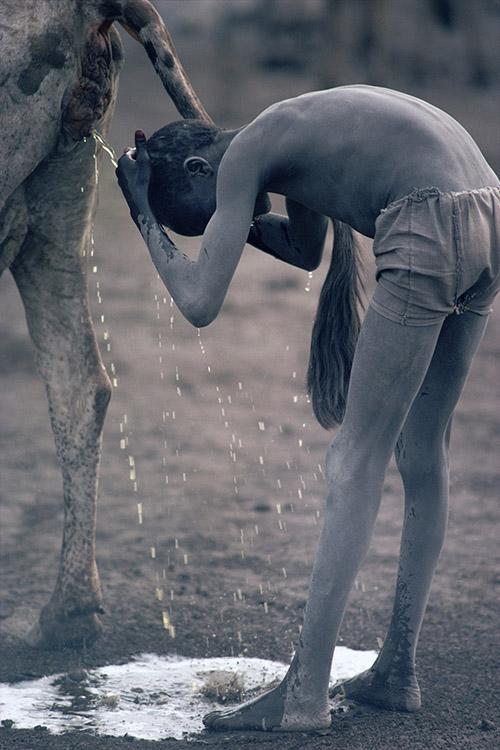 Un ragazzo Nuer si lava i cappelli con l'urina di mucca Jonglei, Sudan del Sud 1981 © Kazuyoshi Nomachi