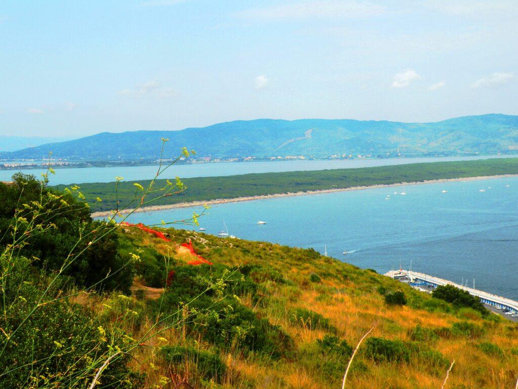 La lunga lingua di sabbia e alberi della spiaggia di Feniglia, che unisce la terraferma all'Argentario. Secondo la tradizione, Caravaggio, colpito da una febbre altissima cadde sulla sabbia e fu poi recuperato da alcuni abitanti del luogo