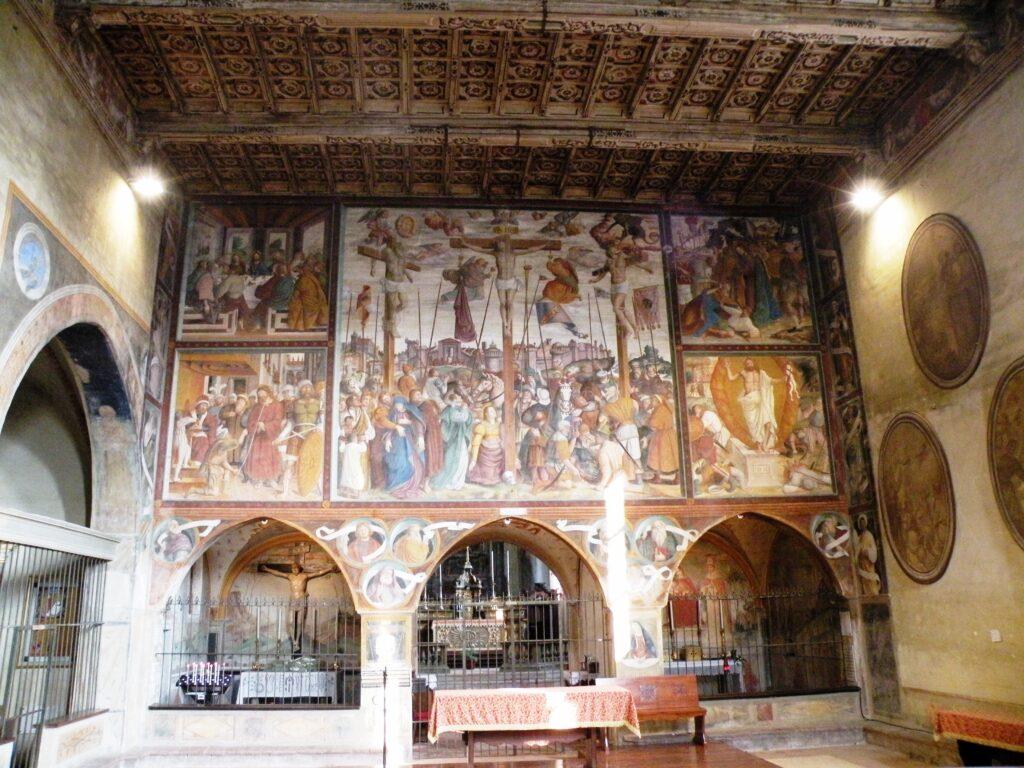 L'interno della chiesa francescana, affrescata dal pittore caravaggino Fermo Stella, uno dei numerosi pittori originari del paese, che avrebbe dato al mondo numerosi artisti, impresari edili e muratori. Le immagini di questo edificio furono certamente osservate dal piccolo Michelangelo