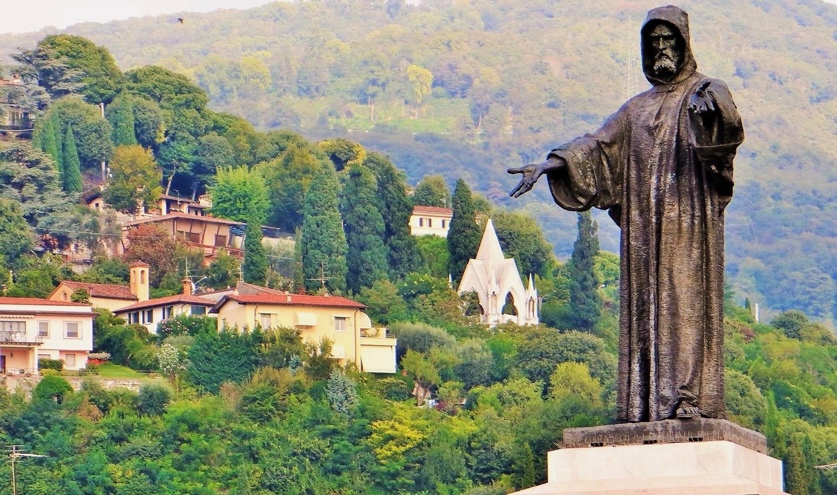 La statua di Arnaldo sembra indicare la Tomba del Cane, edificio neo-gotico progettato da Vantini e costruito sulla collina dei Ronchi