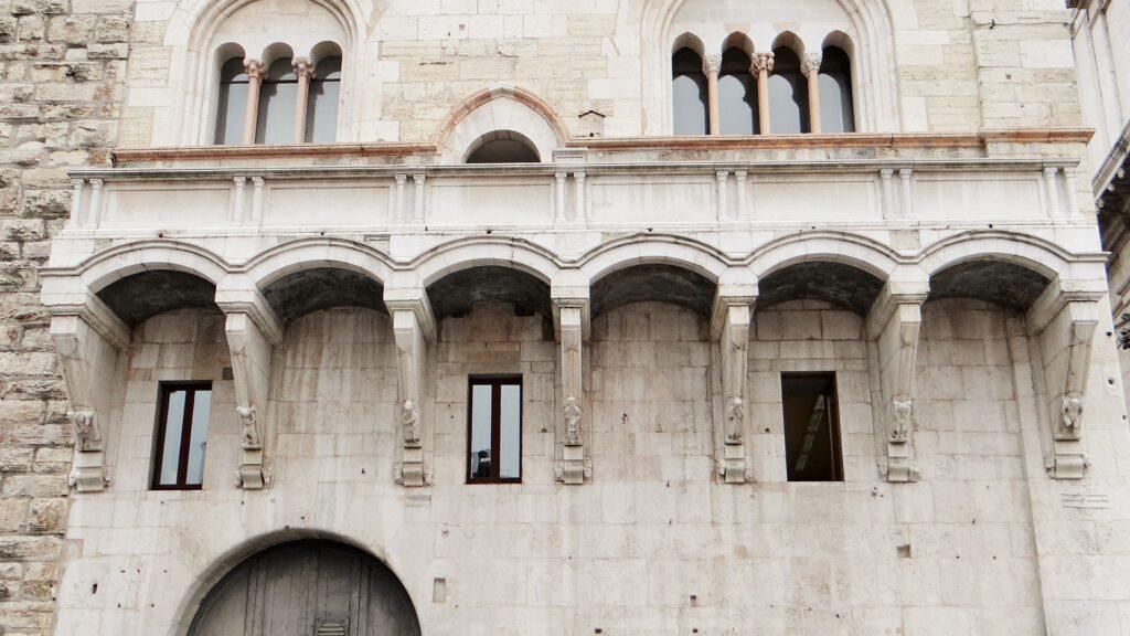 Alla base della loggia del Broletto, le sette piccole sculture