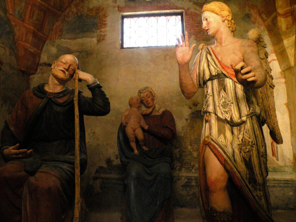 """G.FERRARI e aiuti, Il secondo sogno di Giuseppe (part.), 1520-1530 ca., Varallo,(Vc), Sacro Monte, Cappella IX. Le opere, in terracotta, completate da abiti e da veri capelli offerti dalle monache dovettero costituire un ricordo indelebile per Caravaggio, nonostante alcuni critici affermino il contrario. Il Sacro Monte di Varallo presenta, in questo """"teatro di statue"""", luci radenti, ricavate da apposite aperture che sembrano contenere, in nuce, suggerimenti, trasformati da Merisi in vigorosi dipinti. Nel fondo Peterzano, appartenente al maestro e alla scuola frequentati da Caravaggio, Bernardelli Curuz e Conconi Fedrigolli hanno trovato disegni che segnano un punto evidente di raccordo iconografico tra la bottega e il Sacro Monte"""