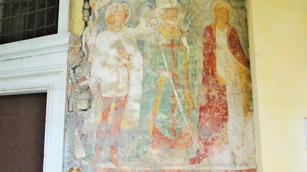 L'affresco del Quattrocento, all'esterno della Rotonda del Santuario di Valverde. L'opera, legata a moduli gotici, mette in evidenza la forte valenza penitenziale del santuario. Sant'Ambrogio impugna il flagello, mentre San Michele, in un abito immacolato, bianco come quello dei Flagellanti che qui confluirono dopo l'apparizione, pesa gli uomini e i loro peccati, al momento della morte