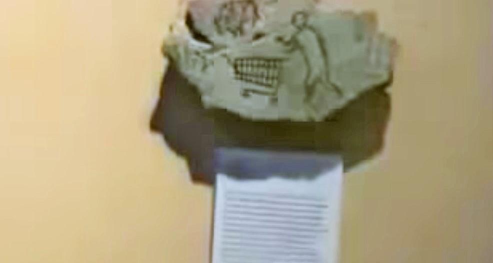 Graffito con bisonte e figura antropomorfa con carrello del supermarket esposto surrettiziamente da Banksy nella sezione archeologica di un museo americano