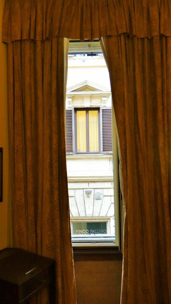 Prima finestra, alla nostra sinistra, della sala. Le tende montate alla mantovana incorniciano la preziosa veduta del portale e di una finestra del palazzo di fronte, con un legante timpano. Qui nacque il poeta Trilussa