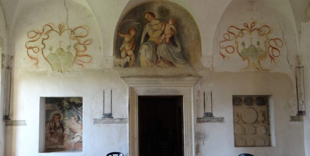 Voltandosi, dopo essere entrato dalla porta, l'oipite notava una lunetta con la figura della Madonna, del Bambino, di San Giovannino e di un Agnello che ricorda le decorazioni di Correggio nella camera della Badessa di Parma (1518-1519). Il ciclo per il refettorio bresciano venne dipinto da Romanino attorno al 1530-1532