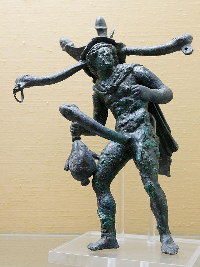 Un tintinnabulum polifallico trovato a Pompei. La forza magica dell'oggetto artistico antico risiedeva nella presenza di più peni, ai quali erano legati campanellini. Il pene, derivato dalle statue di Priapo, è abnorme, trasformato in una sorta di bastone, un'arma di difesa e di offesa. IlProbabilmente la fusione del pene di Priapo, dei tintinnabula e del corallo magico, dà origine al corno rosso della tradizione napoletana