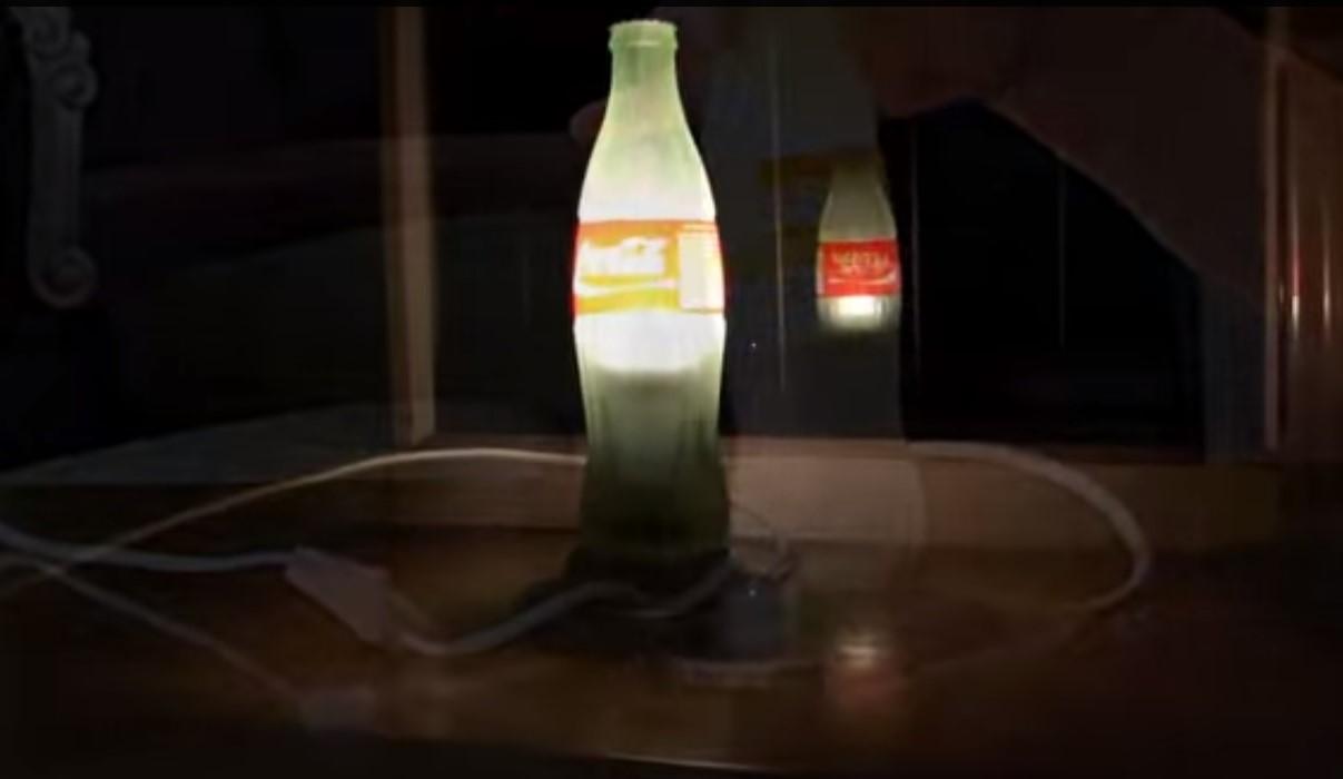 Una lampada da tavolo realizzata con una bottiglietta di vetro di Coca Cola