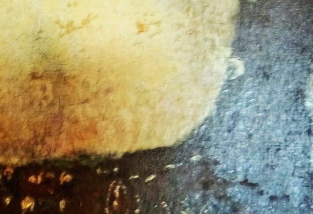 Particolare di un ritratto del Seicento, che presentava velature, quasi completamente scomparse a causa una pulitura radicale. Quello che vediamo è il torace di una donna eil suo corpetto. Osservando con attenzione notiamo lievi tracce delle antiche velature con le quali era stata dipinta la camicetta ed altri punti in cui il colore chiaro è stato rimosso. Appare evidente, nella parte dell'opera alla nostra destra, a livello di tessuto, che la pulitura è andata a ridosso della prima stesura che appare molto secca e poco luminosa. L'eliminazione di tutta la vernice finale ha comportatola perdita delle preeziose velature, che erano collocate tra una stesura della vernice finale e l'altra,come in sandwich