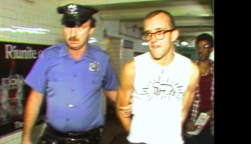 Keit Harin viene ammanettato e portato nella sede della pulizia per aver disegnato con i gessi i suoi omini su un pannello del tunnel della metropolitana di New York