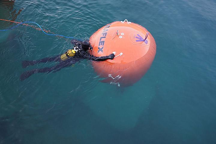 Un sub dirige un grosso pallone che sostiene uno dei numerosi pesi di ancoraggio dei pontili galleggianti. Foto: Wolfgang Volz